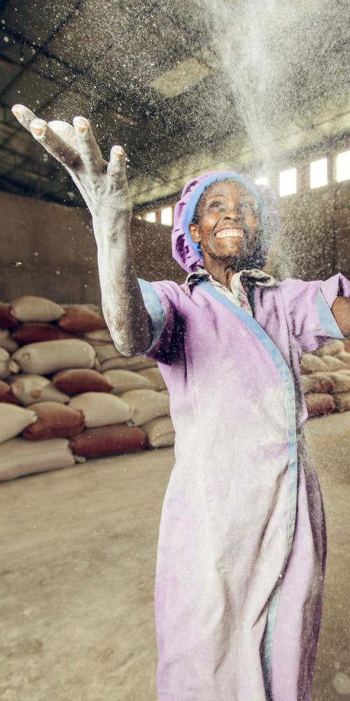 Woman in Ethiopia tossing flour in the air.